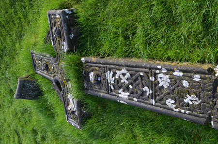 irish countryside: Thick green grass growing out of the ruins of a fallen cross.