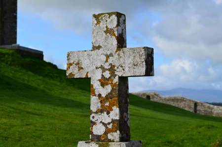 irish countryside: Old stone cross in Ireland with lichen growing on it in Ireland.