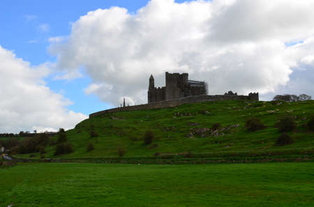 Lush green landscape surrounding the Rock of Cashel in Ireland.