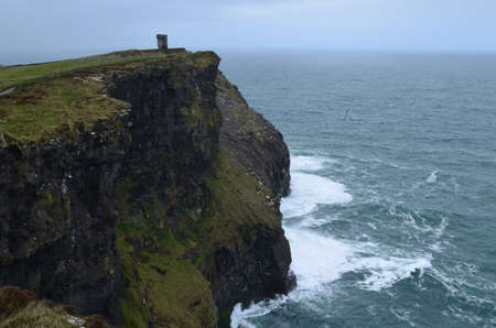 Hag's head standing ont he sea cliff in Ireland on the Cliffs of Moher.