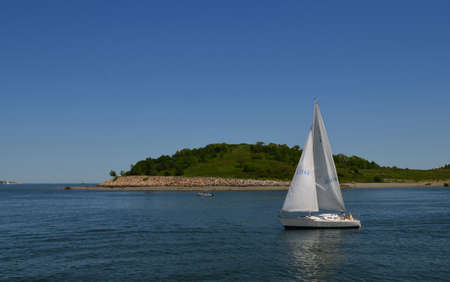 Great view of a sailboat just off shore of the Boston harbor islands.