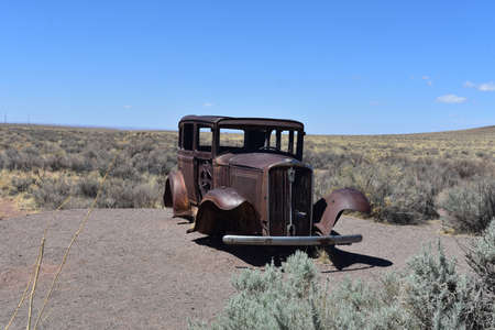 Arizona landscape with a rusted antique car found on Route 66.