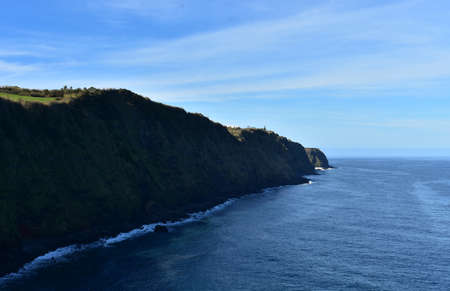 Sao Miguel's coastline with stunning sea cliffs under blue skies.