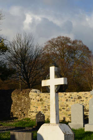 White Christian cross in cemetery at Adare Ireland.