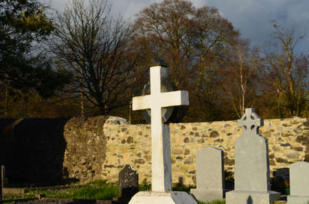 White stone cross in Adare cemetery beside the monastery.