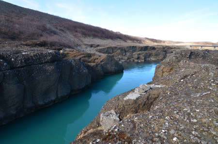 Blue colored river flowing through rocks in Iceland