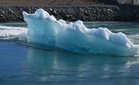 Side view of a large blue glacier in a bay in Iceland