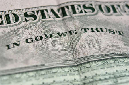 Macro of a five dollar bill with In God We Trust on the back.