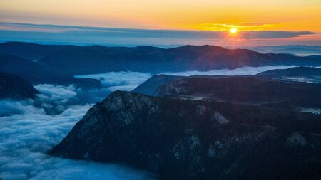 Sunrise above the canyon filled with morning clouds like cotton; bright yellow sun peaking through clouds on the horyzon Stock Photo