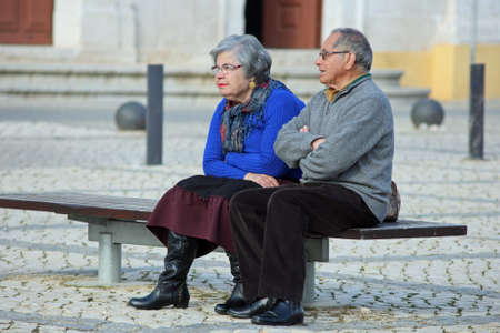 Portimão, Portugal - March 17, 2011: Retired Couple resting on a bench in the center of city. Their view in the future is affected by financial crisis