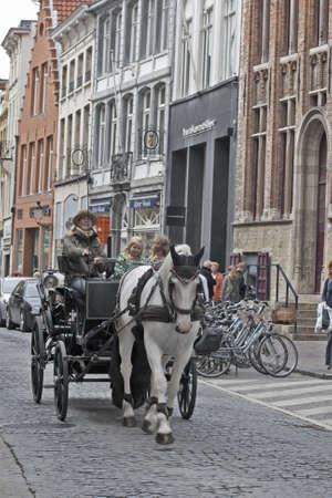 Brugge, Belgien - 28. Mai 2011: Eine Pferdekutsche mit einem Fahrer und Touristen durch die Straßen von zentralen Brugge, Belgien Редакционное