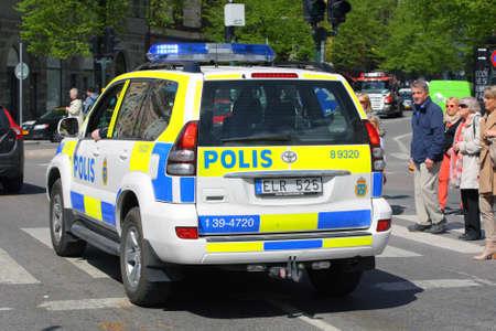 Stockholm, Schweden - 15. Mai 2013: Police Car durch den Einsatz in Stockholm City - schlie? sich zu marschierenden k?lichen Orchester und sorgt f?hre Sicherheit Редакционное