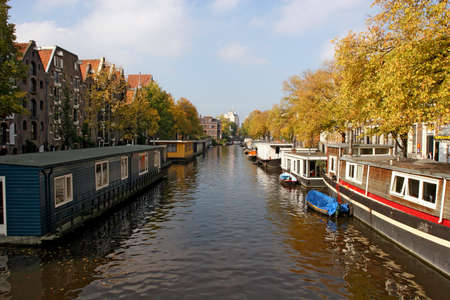 Water Canal with residential houseboats - this is a picture of the city of Amsterdam (Netherlands) - October 11, 2008