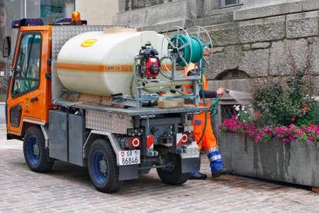 SANKT MORITZ, SWITZERLAND - JULY 13: Worker municipal service takes care of flower arrangements in the summer sufficient watering in Sankt Moritz, Switzerland on July 13, 2015 Редакционное
