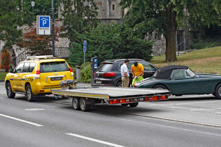 filling out: VADUZ, LIECHTENSTEIN - JULY 17: Service worker towing service helps with filling out the document for towing in Vaduz, Liechtenstein on July 17, 2015