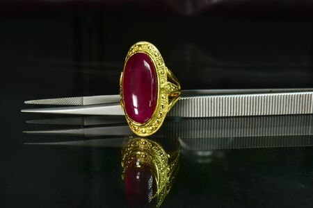 Gold ring Set with rubies, a beautiful red gemstone on the glass floor Reklamní fotografie