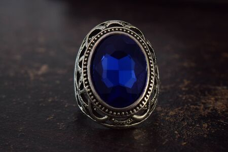 The silver ring is decorated with blue sapphire placed on a wooden floor.