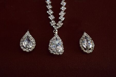 The earrings adorned with diamond were laid on the ground.