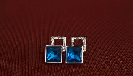 The earrings adorned with aquamarine were laid on the ground.