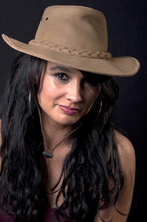 beautiful brunette with cowboy hat with black background photo