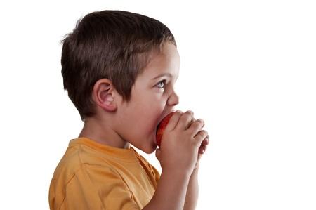 poco: niño comiendo una manzana sobre fondo blanco Foto de archivo