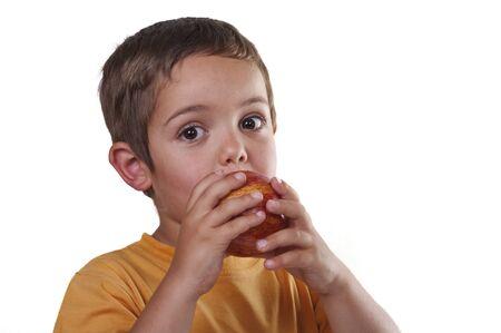 niño comiendo una manzana sobre fondo blanco