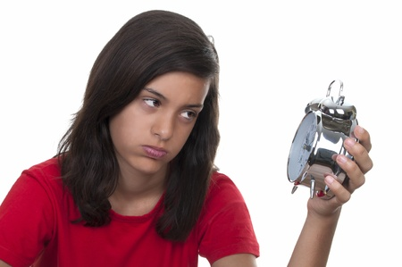 teen girl angry at the alarm clock on white background Stock Photo - 10411734