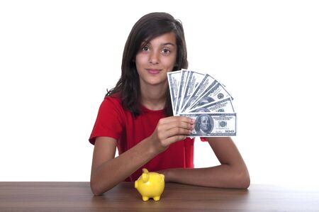 accrue: brunette teen girl with piggy bank and bills of 100 euros on white background