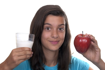 teenage girl with red apple and a glass of milk on white background photo