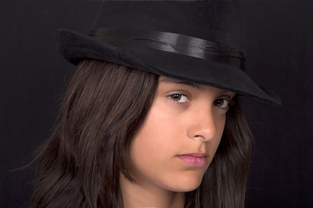 teenage girl with black hat on black background photo