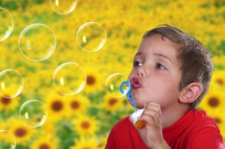 adorable child blowing soap bubbles in a field of flowers photo