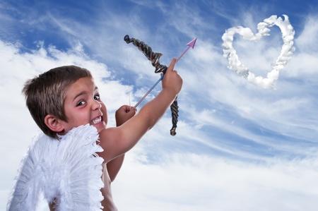 chico adorable vestido de Cupido en el cielo azul