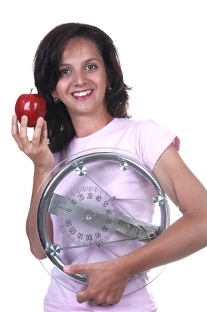 woman with weigh and apple on white background photo