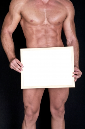 Naked muscular man covering with a box (copy space)  Stock Photo