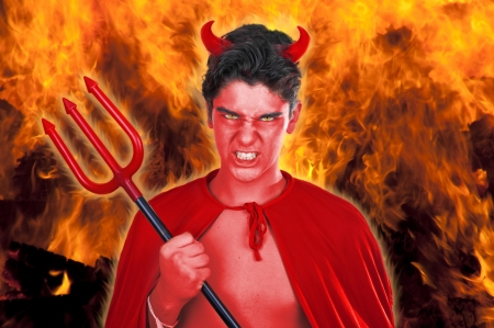 Male actor playing role of daemon on fire background   photo