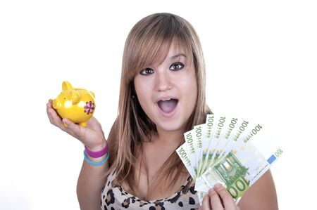 Happy teen holding a piggy bank and bills, isolated on white background  Stock Photo - 14503215