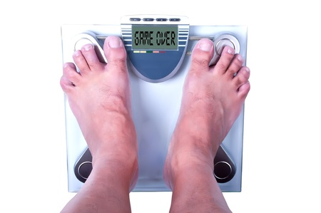 Feet on a bathroom scale with the word game over! on the screen. Isolated.   photo