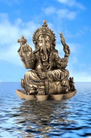 ganesh: Dios hindú Ganesh de agua sobre un poco con un cielo azul