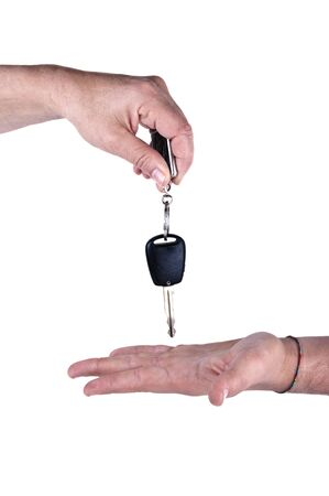 ownership and control: female hand giving car key to male hand on white background