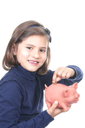 little girl saving money in a piggy-bank Stock Photo - 14518667