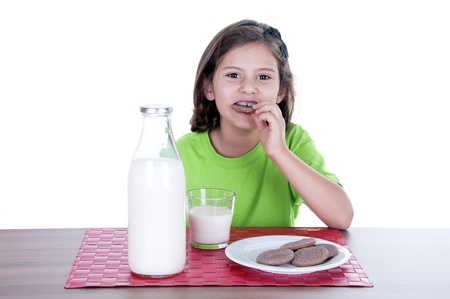 little girl drinking milk and cookies on white background photo