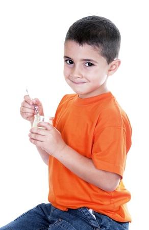 little boy eating yogurt on white background