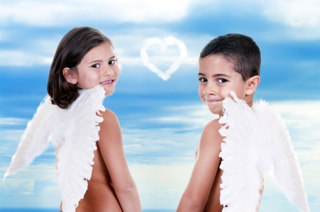 boy and girl dressed as angels in blue sky photo