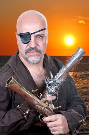 scoundrel: Terribile pirata barbuto con un moschetto in sfondo del tramonto