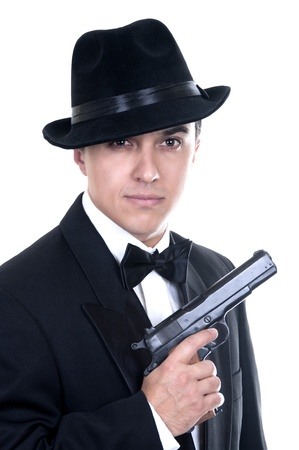 organized crime: Man in suit draws vintage handgun, white collar outfit.  Stock Photo