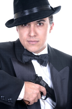 fedora: Man in suit draws vintage handgun, white collar outfit.  Stock Photo