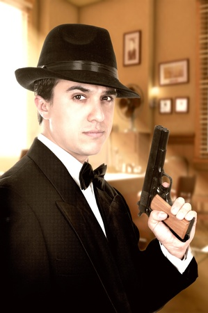 Man in suit draws vintage handgun, white collar outfit.  photo
