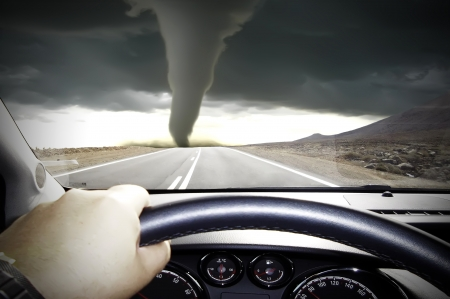 The car rushes on road towards to a tornado