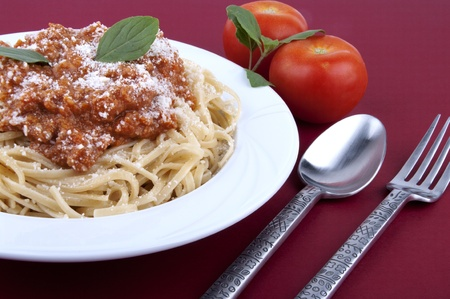 Spaghetti bolognese on red table photo