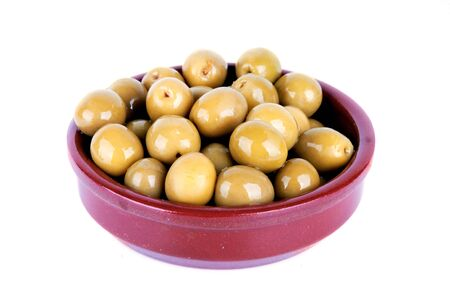 watered: Green olives watered with oil in a clay plate